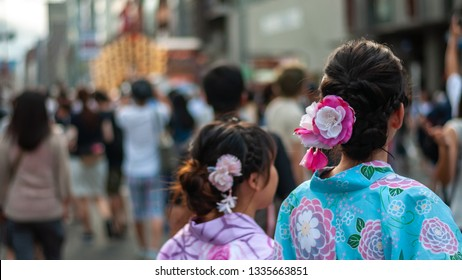 KYOTO, JAPAN - JULY 15, 2016 : Two Japanese girls clad in traditional colorful and beautiful yukata with pretty hair ornaments walking along Karasuma street in Kyoto City's famous Gion Festival.