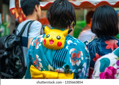 KYOTO, JAPAN - JULY 15, 2016 : Japanese girl clad in traditional colorful and beautiful yukata with a Pikachu mask hung on the back of her neck, seen in Kyoto City's famous Gion Festival.