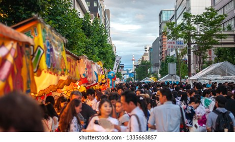 KYOTO, JAPAN - JULY 15, 2016 : A huge crowd of people walking along Karasuma street in Kyoto City's famous Gion Festival, with a view of Kyoto Tower in the background.