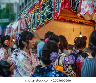 KYOTO, JAPAN - JULY 15, 2016 : Several cute Japanese girls clad in traditional beautiful yukata with pretty hair ornaments queuing up in front of a food stall in Kyoto City's famous Gion Festival.