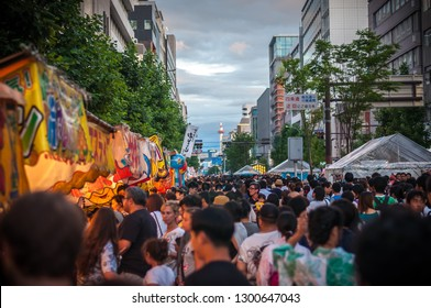 KYOTO, JAPAN - JULY 15: A huge crowd of a mix of Japanese locals and foreign tourists walking along Karasuma street in Kyoto City's famous Gion Festival, with a view of Kyoto Tower in the background.