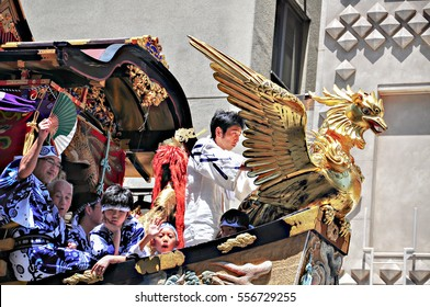 Kyoto, Japan - July 17, 2011: People riding on  highly decorated float participating in Gion Festival, Kyoto, Japan