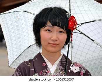 KYOTO, JAPAN - JUNE 21, 2013: Young Japanese woman with flower in hair wears a traditional kimono and poses for the camera under her umbrella, on a rainy day at the Yasaka Shrine, on June 21, 2013.
