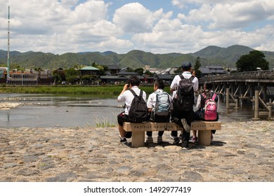 Kyoto, Japan - June 25, 2019: Student schoolchildren are sitting on a bench near Katsura river