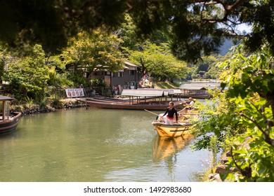 Kyoto, Japan - June 25, 2019: Japanese muscular man leads a boat on Katsura river