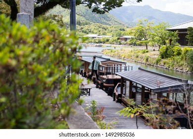 Kyoto, Japan - June 25, 2019: Japanese man gets out of the boat near Katsura river