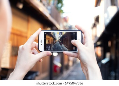 Kyoto, Japan - June 25, 2019: Girl take picture of quiet little street of Kyoto near Gion district with Iphone, instagram blogger concept