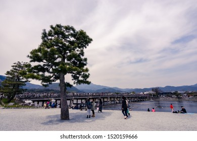 Kyoto, Japan - Mar 30, 2016: Tourists walking on Togetsu-kyo wooden and old bridge over Katsura River in Saga Arashiyama, a well-known famous place in Kyoto.