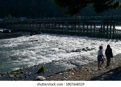 Kyoto / Japan - March 10, 2020: Two Japanese girls walking next to Katsura river and Togetsukyo bridge in Kyoto Japan
