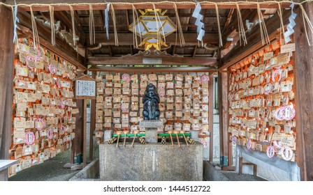 Kyoto, Japan - March 11, 2019 : Temizuya (Water ablution Pavilion) surounded by Ema plaques at Higashi Tenno Okazaki Shrine, or Usagi Jinja. Associated with the fertility and easy child birth deities.
