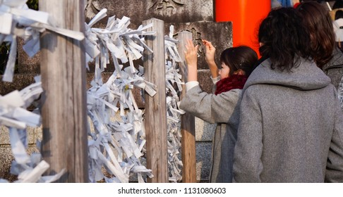 Kyoto, Japan - March 2017: Japanese kid trying for o-mikuji. It is a random fortunes written on strips of paper at Shinto shrines and Buddhist temples.