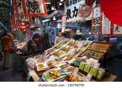 KYOTO, JAPAN - MARCH 23: Staff and customers at a stall selling cooked fish at Nishiki food market in Kyoto on 23rd March 2012. The market is known for it's diversity of food stalls and restaurants.