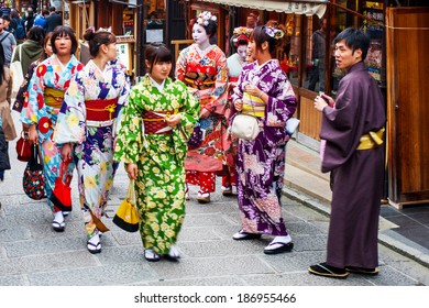 KYOTO, JAPAN - MARCH 25, 2014: Young Japanese women wearing traditional Kimono for cherry blossom viewing in the Gion district of Kyoto on March 25, 2014. Gion is Kyoto's most famous geisha district.