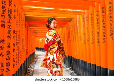 KYOTO, JAPAN - March 25. 2017.: Nomen in kimono walking at Red Torii gates in Fushimi Inari shrine, one of famous landmarks in Kyoto, Japan. Selective focus on women wearing traditional japanese