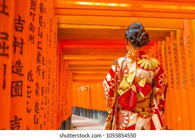 KYOTO, JAPAN - March 25. 2017.: Women in kimono walking at Red Torii gates in Fushimi Inari shrine, one of famous landmarks in Kyoto, Japan. Selective focus. Women wearing traditional japanese kimono