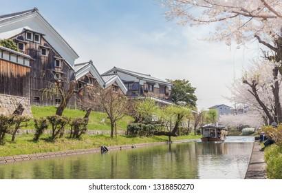 Kyoto, Japan - March 27 2018: Jikkokubune boat with tourists passing Gekkeikan Okura Sake Museum