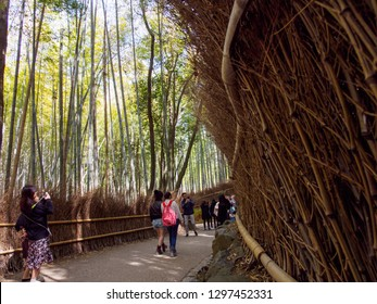 KYOTO, JAPAN - MARCH 30, 2018: Wide view of tourists walking past the twig fencing along the famous bamboo groves of Arashiyama Forest. Travel and tourism.