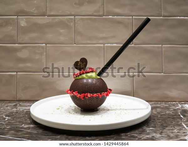 Kyoto, Japan - March 31, 2019: Seasonal strawberry smoothie in a spheric chocolate cup at Godiva boutique in Daimaru department store