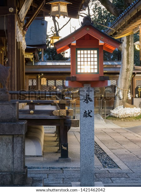 Kyoto, Japan - March 9, 2019: Wooden lantern on a stone basement in Goo-jinja shrine