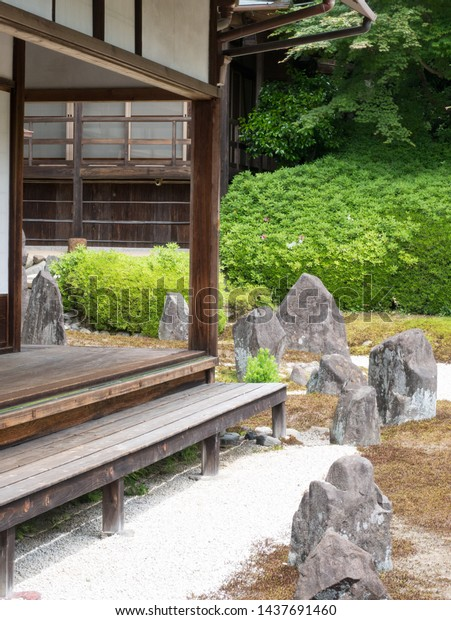 Kyoto, Japan - May 10, 2019: Part of engawa veranda and Japanese stone garden of a quiet Komyoin temple designed by famous landscape historian and designer Shigemori Mirei