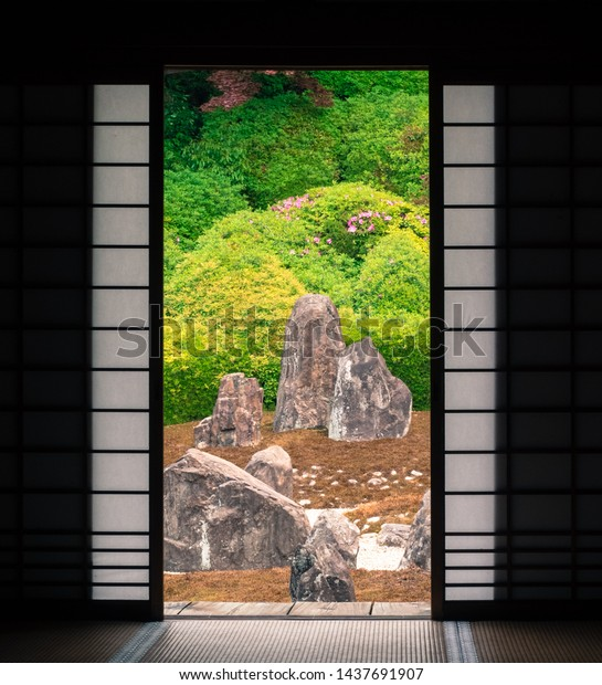 Kyoto, Japan - May 10, 2019: view on Japanese Stone garden of a quiet Komyoin temple designed by famous landscape historian and designer Shigemori Mirei through the poened fusuma sliding doors