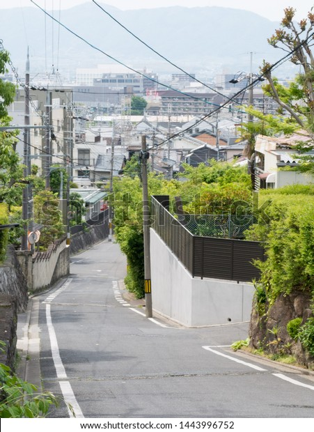 Kyoto, Japan - May 10, 2019: small empty street in the residential area of Kyoto during the day. Electric poles and strings of cables - typical scenery in Japan