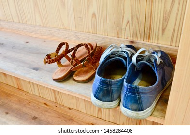 Kyoto, Japan - May 15, 2014. Shoes Off -  Picture of a pair of shoes and a pair of sandals on a wooden background taken off to enter a temple in Japan.