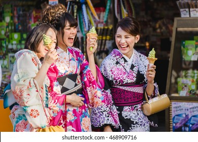 KYOTO, JAPAN - MAY 19, 2014: Laughing japanese women with ice-cream wearing traditional Kimono walk on the streets of Kyoto, Japan