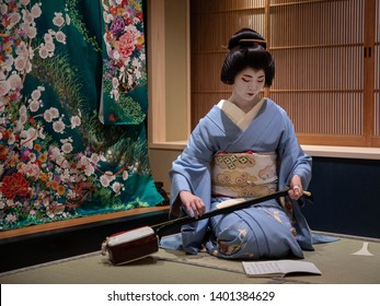 Kyoto, Japan - May 19, 2019: Young geisha in training, called a maiko, tunes her instrument prior to performance in traditional japanese inn