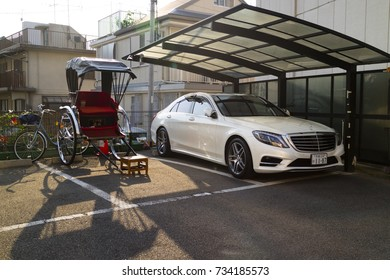 Kyoto, Japan - May 21, 2017: Rickshaw and mercedes car together parked in the street showing old compared to new transport