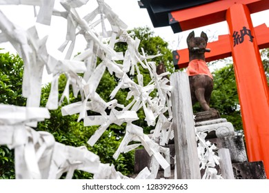 KYOTO, JAPAN - MAY 25,2017. One of popular activities at the Fushimi Inari Shrine in Kyoto, Japan for tourists and Japanese people is to hang fortune-telling paper strips .