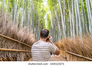Kyoto, Japan - May 29, 2019: A man takes a photo of his family in the famous Bamboo Grove, a popular tourist site in Arashiyama.