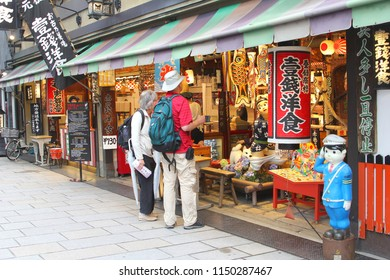 KYOTO, JAPAN - May 31, 2018. Elderly tourist couple is watching colorful souvenirs, home decorations and Japanese lanterns in art shop at the night market in Gion district. Holiday shopping in Japan.