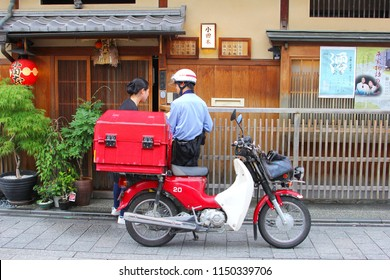 KYOTO, JAPAN - May 31, 2018. Japanese post man on motorbike with red delivery box delivers mail to a woman in charming old street with traditional wooden houses in Gion district. City transportation.