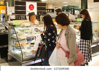 KYOTO, JAPAN - May 31, 2018. Japanese female vendor is selling and women are buying fresh food in delicatessen shop at indoor Nishiki market.