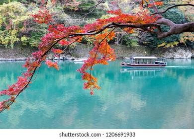 Kyoto, Japan - Nov 16, 2017 : Tourists in boat to bring enjoy autumn colors along katsura river to Arashiyama mountain in Kyoto, Japan