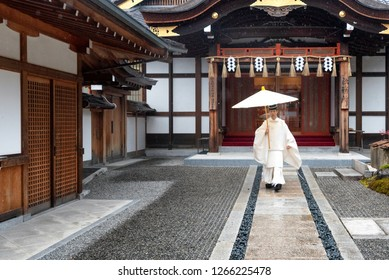 KYOTO, JAPAN - NOV 22: Young kannushi, also called shinshoku, taking care of the Fumishi Inari Shrine in Kyoto, Japan on a rainy day on November 22, 2018.