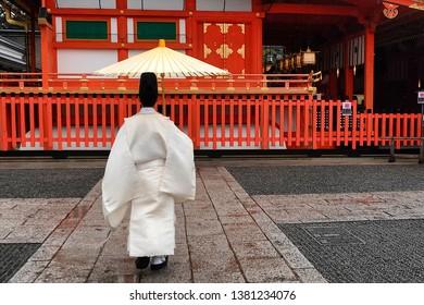 KYOTO, JAPAN - NOV 22: Young kannushi, also called shinshoku, taking care of the Fushimi Inari Shrine in Kyoto, Japan on November 22, 2018.