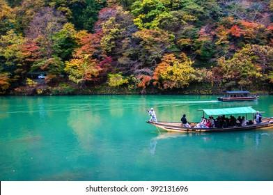 Kyoto, Japan - NOV 23, 2012: Traditional tourist boat pass on the emerald color Katsura river along the beautiful autumn leaves in the cold tone, Arashiyama, Kyoto, Japan