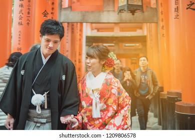 KYOTO JAPAN - Nov 30, 2017: The couple in japanese traditional wedding clothing walk through the Fushimi Inari Taisha, Fushimi Inari Shrine in Kyoto, Japan.
