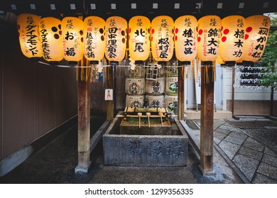 KYOTO, JAPAN - NOVEMBER 09, 2018: Japanese paper lanterns hanging on water ablution pavilion for a ceremonial purification at Nishiki Tenmangu Shrine in Kyoto, Japan