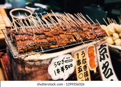 KYOTO, JAPAN - NOVEMBER 09: Grilled unagi or fresh water eel on sticks as street food at Nishiki market in Kyoto, Japan. Market is a great place to find seasonal foods and Kyoto specialties.