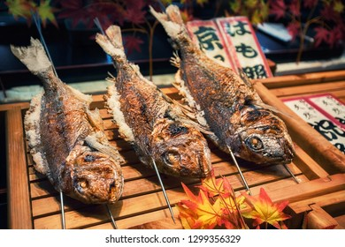 KYOTO, JAPAN - NOVEMBER 09: Grilled fishes on sticks as street food at Nishiki market in Kyoto, Japan. Market is a great place to find seasonal foods and Kyoto specialties.