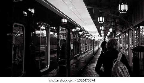 Kyoto, Japan - November 15, 2013: People walking on the retro looking platform of Hankyu train line in Arashiyama