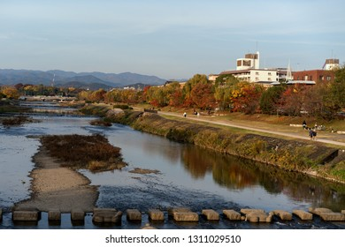 Kyoto,, Japan - November 18 2016 : Katsura river is the main river that cut across Kyoto city Japan  in autumn with people walking by the river and mountain background