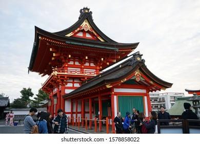 Kyoto, Japan November 19,2019 : Fushimi Inari Shrine or Fushimi Inari Taisha famous for its thousands of vermilion torii gates and Fox or Kitsune statue wearing red bib holding a symbolic  in mouth