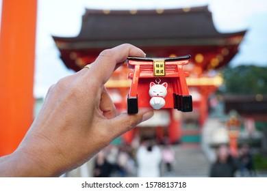 Kyoto, Japan November 19,2019 : Souvenir  Fushimi Inari Shrine or Fushimi Inari Taisha famous for its thousands of vermilion torii gates and Fox or Kitsune statue wearing red bib holding a symbolic