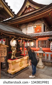 Kyoto, Japan -November 2, 2018: Young girl praying in front of Jinja-Jishu shrine at the famous Kiyomizu-dera Buddhist Temple, in Gion District, Kyoto, Japan.