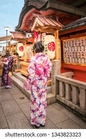 Kyoto, Japan -November 2, 2018: Young girls in traditional Japanese costume praying in front of Jinja-Jishu shrine at the famous Kiyomizu-dera Buddhist Temple, in Gion District, Kyoto, Japan.