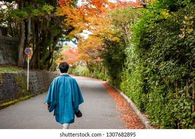 KYOTO, JAPAN - NOVEMBER 23, 2016: Landscape photo of a lone Japanese man clad in traditional kimono walking on an empty street with colourful, beautiful autumn foliage right outside Maruyama Park.